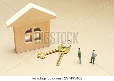 Two People Are Standing Near A Wooden House. Concept Of Real Estate. Buying And Selling An Apartment