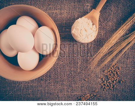 Top View Of Wheat Ears, Grains, Wooden Spoon With Flour And Bowl With White Chicken Eggs. Culinary B
