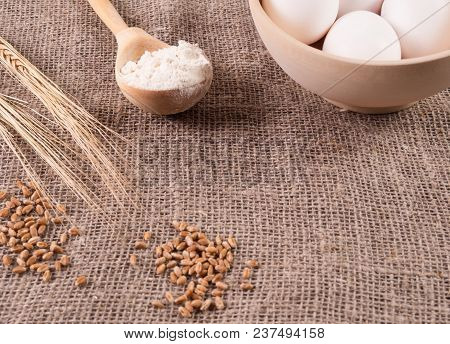 Lying On The Background Of Sacking Grain And Ears Of Wheat, A Wooden Spoon With Flour And Eggs