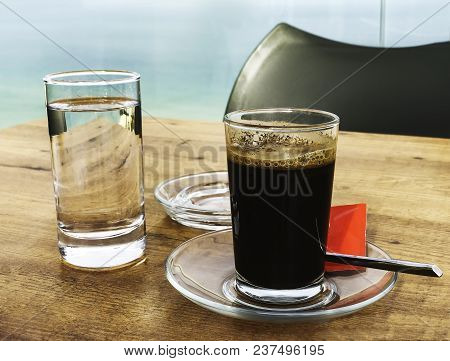 Strong And Dark Coffee In A Glass Served With A Glass Of Water On A Wooden Table Outdoors In A Cafe