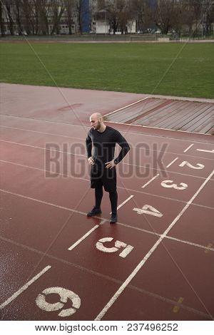 one man looking down, sport venue, sad depressed.