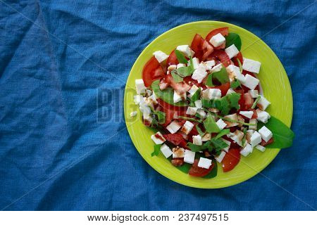 Healthy Vegetarian Salad Of Red Tomatoes, White Cheese And Fresh Greens, Seasoned With Pomegranate S
