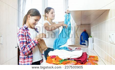 Teenage Girl Helping Mother Sorting Clothes In Laundry Room