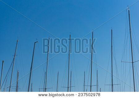 Abstract Background Of Yacht Poles, Masts Against Blue Sky On The Background
