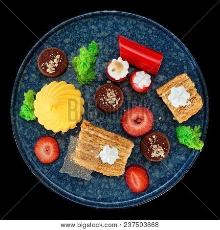Set of various desserts in stone plate isolated on black background