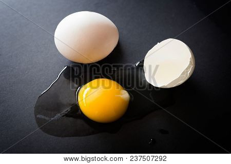 Horizontal Low Key Image Of A Raw Organic Egg Cracked Open Onto A Black Background.