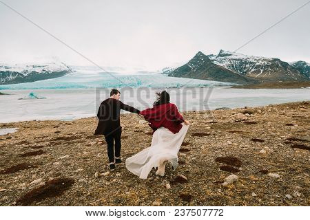Iceland Wedding In Glacier Lagoon. Bride And Groom Runs Together. Rear View. Copy Space