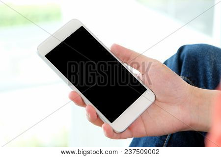 Man Hand Holding Smartphone With Blank Screen On Background For Mock Up, Template, Technology And Li