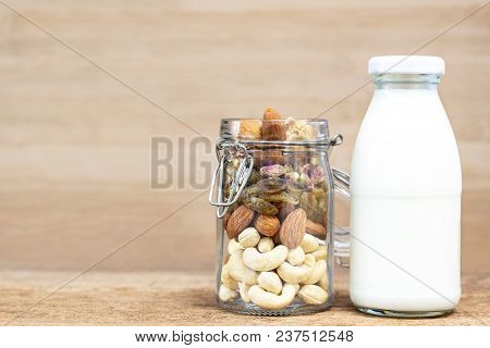 A Variety Of Nuts Into A Bottle Glass And A Glass Of Milk On The Wooden Background, Such As Figs, Al
