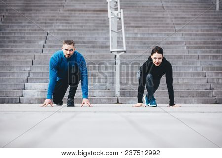 Young athletic couple in a steady position crouching. Fit lifestyle. Competition and race.