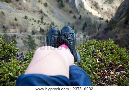 woman's feet in hiking boots sitting on top of mountain