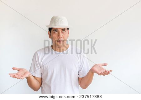 Asian Man Wear White Hat Raise Hand Up With Boring Expression Emotion At White Wall Background.looki