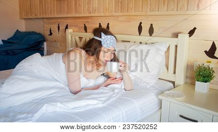 Sleepy Woman Lying In Bed And Drinking Coffee