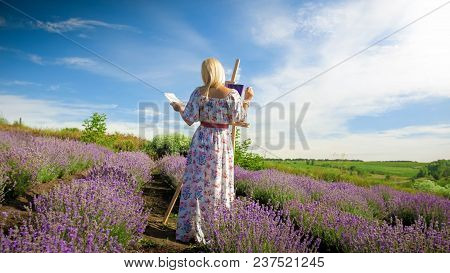 Rear View Photo Of Young Woman In Long Dress Painting Picture Of Beautiful Lavender Field At Provenc