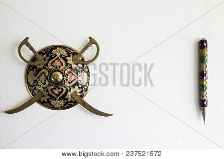 Decorated Sword And Round Shield And Pen Isolated In White Background With Copy Space For Text. Anti