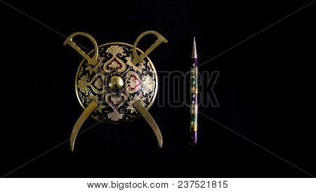 Decorated Round Sword And Shield And Pen Isolated In Black Background With Copy Space For Text.antiq