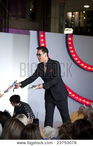 SOUTHAMPTON, UK - SEPT. 22: Gok Wan signs copies of his autobiography from the catwalk in West Quay Shopping Centre during filming of his television show