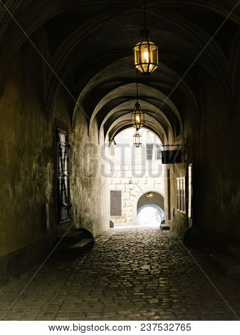 Narrow dark street illuminated by street lamps. Stone pavement in the old town Cesky Krumlov, Czech Republic