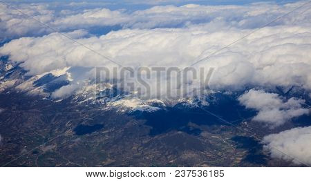 White heavy clouds background hanging on blue sky over mountain. Aerial photo from airplane's window.