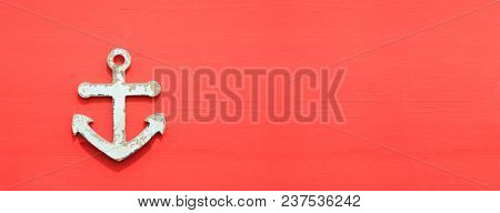Anchor symbol on aged surface. Peeled sign, red board background, copyspace, banner.