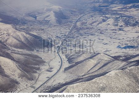Snowy mountains background, highway between them.  Aerial photo from rplane's window.