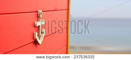 Anchor on red aged surface. Blurred, empty sandy beach, blue sky, sea background. Space for text, banner, close up view.
