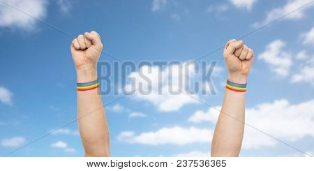 lgbt, same-sex relationships and homosexual concept - close up of male hands wearing gay pride awareness wristbands showing fist over blue sky and clouds background