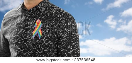 lgbt, same-sex relationships and homosexual concept - close up of man with gay pride rainbow awareness ribbon on his chest over blue sky and clouds background