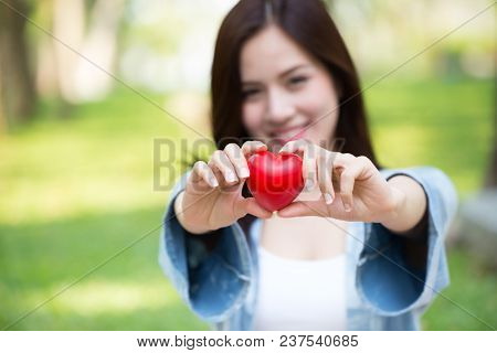 Giving Love Together Concept: Cute Asian Woman Hold Red Heart For Loving Sharing Lovely