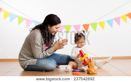 family, holidays and people concept - happy mother applauding for little daughter playing with ring pyramid baby toy on birthday party