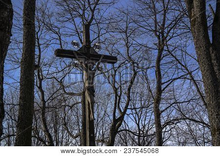 An Old, Rugged, Wooden Cross Stands Against A Pure Deep Blue Sky.