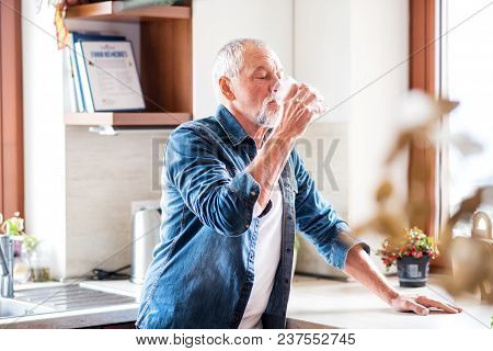 Senior Man In The Kitchen. An Old Man Inside The House, Drinking Water.