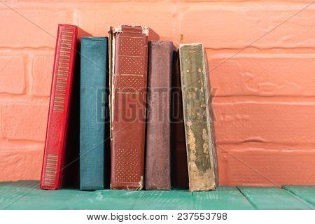 Books On The Background Of A Brick Wall. Bookshelf
