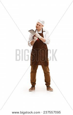 Bored Butcher Posing With A Cleaver Isolated On White Studio Background. The Young Caucasian Male Mo