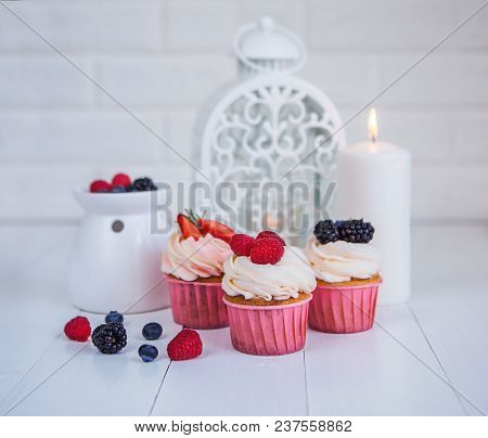 Delicious Cupcakes With Berries On A White Background