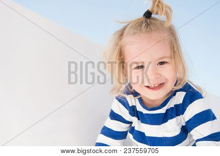 Little Boy Smile In Navy Clothes. Happy Child Enjoy Sunny Day. Kid Smiling With Blond Hair Ponytail.