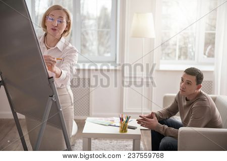 Creative Process. Jovial Senior Psychologist Standing While Staring At Whiteboard