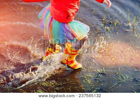 Faceless Active Girl In Colorful Outfit And Gumboots Running In Water Of Puddle Having Fun In Sunset