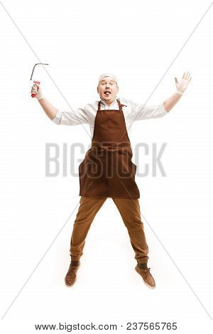 Smiling Butcher Jumping With A Cleaver Isolated On White Studio Background. The Young Caucasian Male