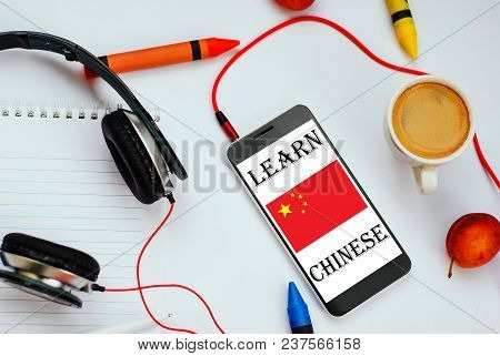 Smartphone With Chinese Flag And Headphones. Concept Of Chinese Learning Through Audio Courses