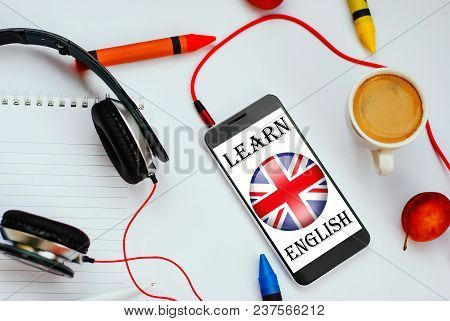 Smartphone With English Flag And Headphones. Concept Of English Learning Through Audio Courses