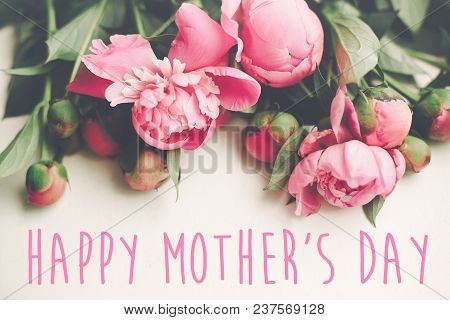 Happy Mother's Day Text On Pink Peonies Bouquet On Rustic White Wooden Background, Top View. Floral