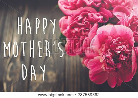Happy Mother's Day Text On Pink Peonies Bouquet On Rustic Dark Wooden Background In Light. Floral Gr