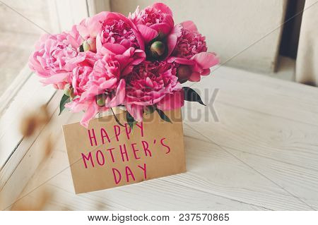 Happy Mother's Day Text On Craft Card And Pink Peonies Bouquet On Rustic White Wooden Window In Ligh