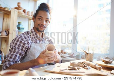 Portrait of young mixed race man holding small clay vase in workshop and looking at camera with satisfied smile
