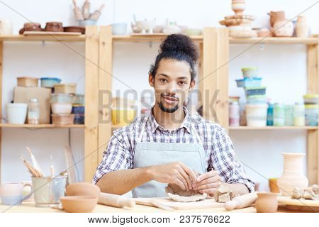 Portrait of young confident mixed race man modeling clay pot in workshop and looking at camera