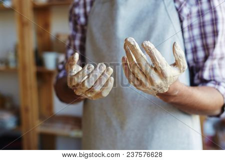 Unrecognizable male ceramist standing in workshop with hands in clay after making earthenware on pottery wheel