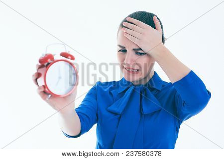 Portrait Of Shocked Brunette Woman With Alarm Clock Over White Background