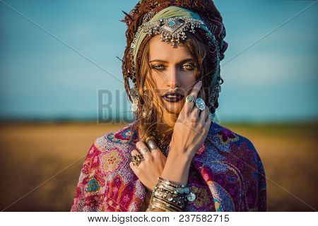 Magnificent fashion woman posing in boho style clothes in the rays of the sunset. Outdoor fashion. Gypsy style. poster
