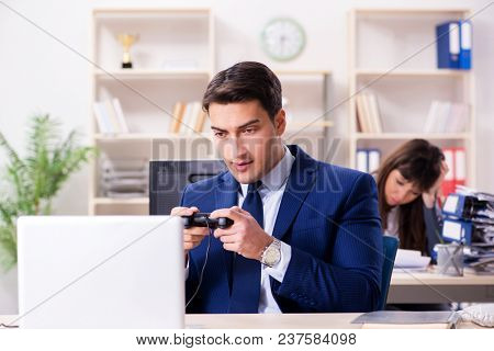 Man playing games in office while colleague is busy